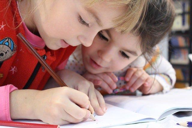 Dvě děvčátka brunetka a blondýnka sklánějící se nad sešitem, do kterého jedna kreslí