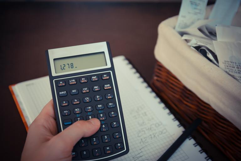 prst počítající na kalkulačce