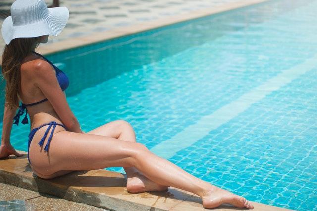 žena v plavkách se světlým kloboukem ležící na kraji bazénu