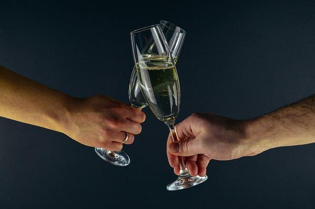 ruce držící sklenice se šampaňským